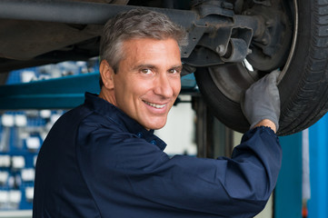 Mechanic In Workshop Changing Tire