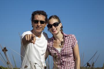Hombre señalando a cámara junto a su pareja