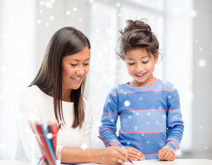 mother and daughter with coloring pencils indoors