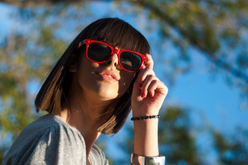 Teenage girl with sunglasses under the trees