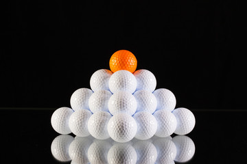 Pyramid of golf balls on a black background