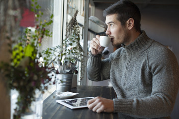 Handsome Man Drinking Coffee And Using Tablet