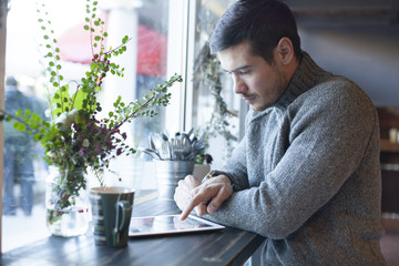Handsome Man Using Tablet Computer Indoor and Drinking Tea