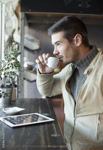 canvas print picture Handsome Man Drinking Coffee And Using Tablet