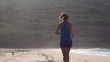 Athletic young woman running on the beach, slow motion