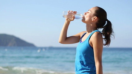 Young smiling woman drinking water after jogging , slow motion