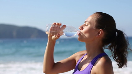 Close up shot of woman drinking water after jogging, slow motion