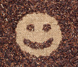 Red rice forming a smiley face on burlap fabric