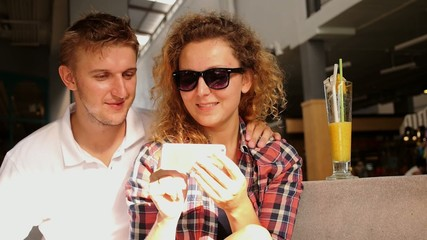 Young Couple Using Smartphone Browsing the Web in Cafe and