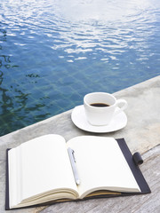 Coffee and Book with Pen by Swimming Pool Travel Background
