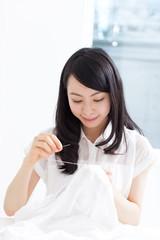 Yシャツにボタンを付ける女性