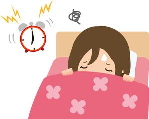 鳴っている目覚ましとベッドの中の女性