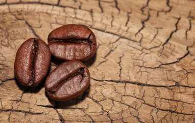 Three Coffee Beans on wooden background. Macro