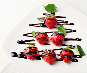 Strawberries  in chocolate sauce on  white plate.