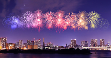 Fireworks celebrating over Tokyo cityscape at nigh