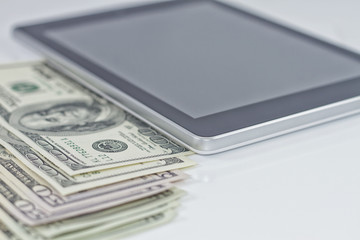 Tablet-PC and dollars on white background