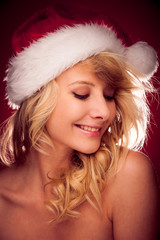 Glamorous young woman with Santa claus hat sending best  wishes