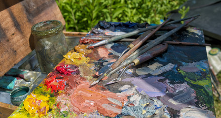 Artistic equipment: paint, brushes and art palette.
