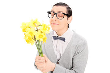 Young man smelling a bunch of yellow tulips