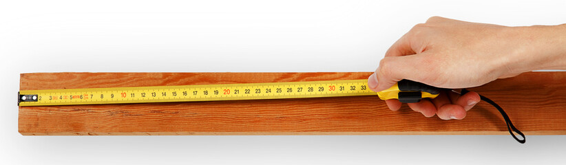 Close-up of a male hand using measuring tape on wooden board