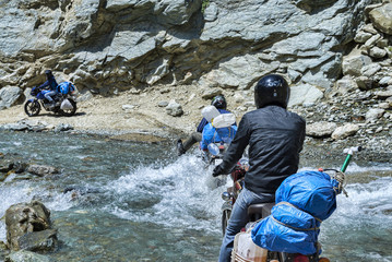 Three bikers riding through mountain river wade on bikes