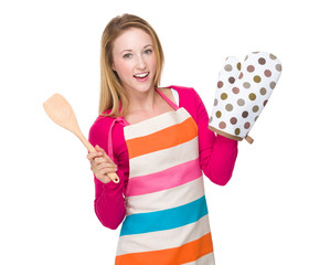 Housewife with oven gloves and wooden turner