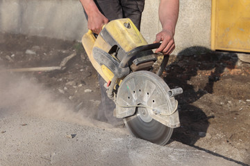 Construction site, worker cut asphalt with saw blade toll