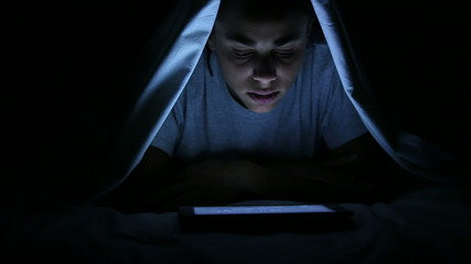 Woman Watching Horror Movie on Digital Tablet under Bed Sheets