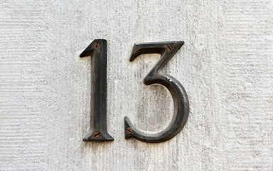 Closeup image of an old rusted metal number 13