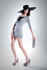 Hübsche junge schlanke Frau in Model Pose mit Hut und Clutch