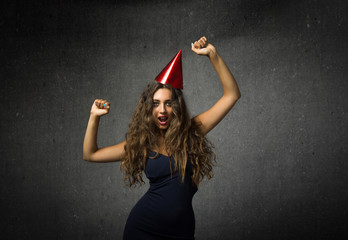 girl dancing with pointed party hat on head