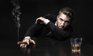 Attraktiver Mann mit Zigarre und Whiskey