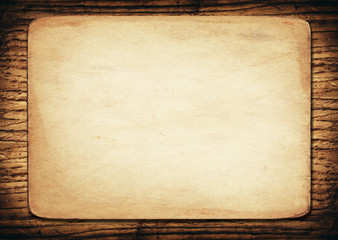 Old paper on dark wooden wall
