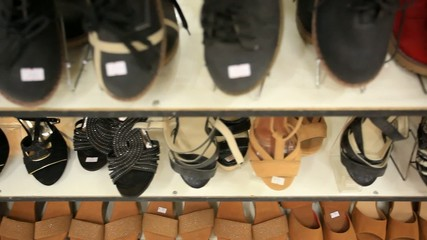 Rows of elegant, colored women's shoes on store shelves. HD.