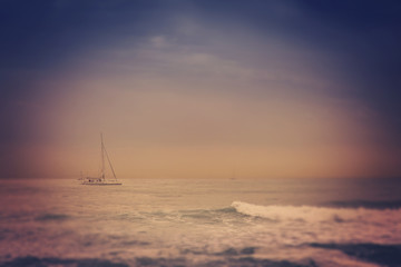 blurred retro image of small yacht in the sea, with tilt shift e