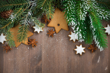 wooden background with fir branches and cookies, horizontal