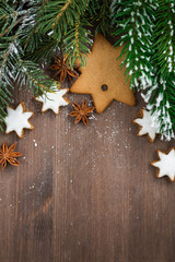 wooden background with fir branches and cookies, top view