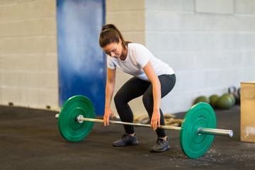 Woman Lifting Barbell At Gym