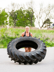 Athlete Doing Tire-Flip Exercise On Street