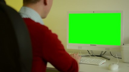 man works on computer - green screen - office