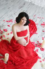 Portrait of a beautiful pregnant woman in red chiffon shawl