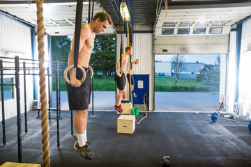 Athletes Exercising On Gymnastic Rings At Healthclub