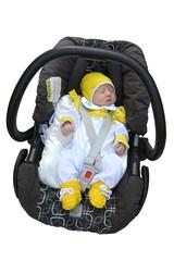 The newborn child sleeps in a children's car seat