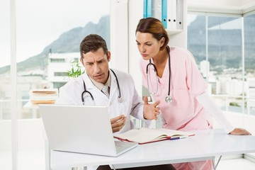 Doctors using laptop at medical office