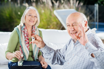 Senior Man Gesturing Okay While Playing Rummy With Woman