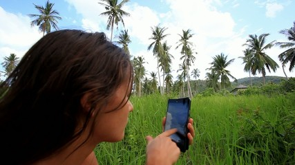 Young  woman uses mobile phone. Jungle in Koh Samui, Thailand.