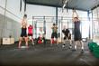 Athletes Lifting Kettlebells in Cross Fitness Box