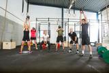 Fototapety Athletes Lifting Kettlebells in Cross Fitness Box