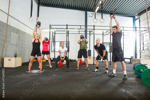 Fotobehang Gymnastiek Athletes Lifting Kettlebells in Cross Fitness Box