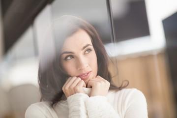 Brunette in white wool jumper thinking
